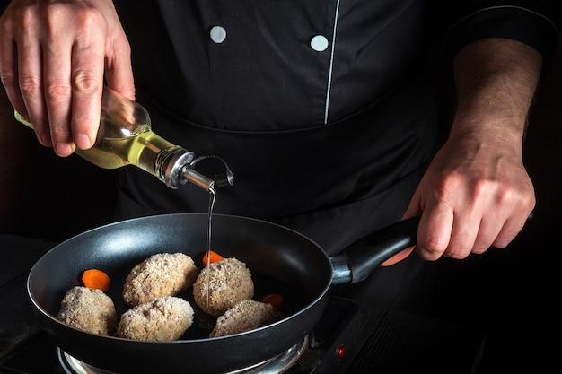 Cocinar chuletas de ternera en una sartén con las manos del cocinero para copiar el menú del restaurante de texto espacial