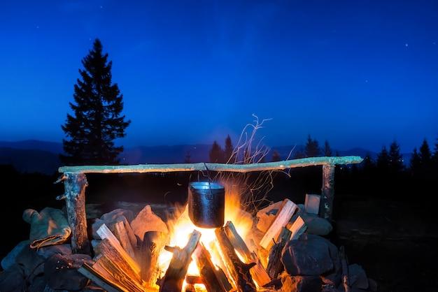 Cocinar la comida en la olla en llamas bajo un cielo azul con muchas estrellas