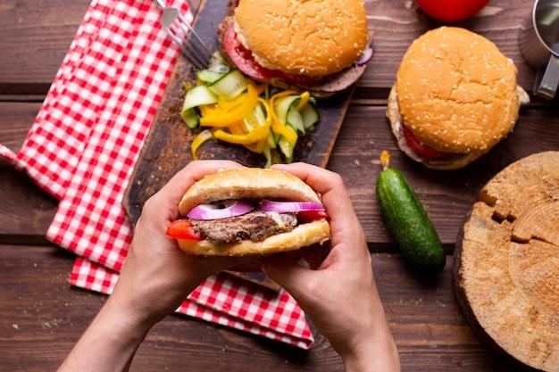 Cocinar deliciosas hamburguesas en casa, hamburguesa en manos del hombre