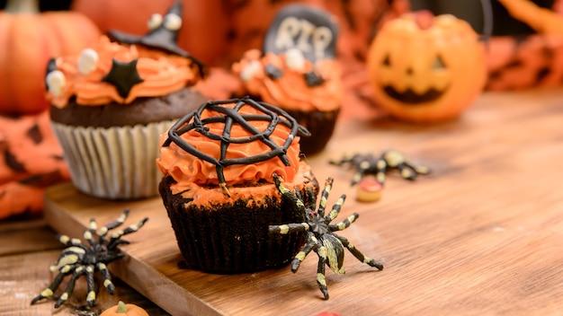 Cocinar deliciosos pasteles caseros y decorar cupcakes para la fiesta de halloween. postre dulce y decoración para fiesta en casa.