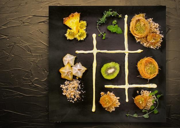 Cocinar dulces postres de pastelería de ramadan tradicional turco kunafa (kadaif, baklava), kiwi, ananas, nueces, fondo oscuro composición de arte de placa.
