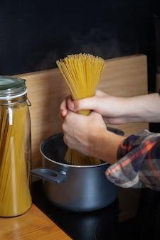 Cocinar los espaguetis en una olla con agua hirviendo, las manos masculinas ponen la pasta en la sartén