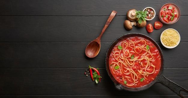 Cocinar espaguetis de pasta italiana casera con salsa de tomate en una sartén de hierro fundido servido con ají rojo, albahaca fresca, tomates cherry y especias sobre una mesa de madera rústica negra.