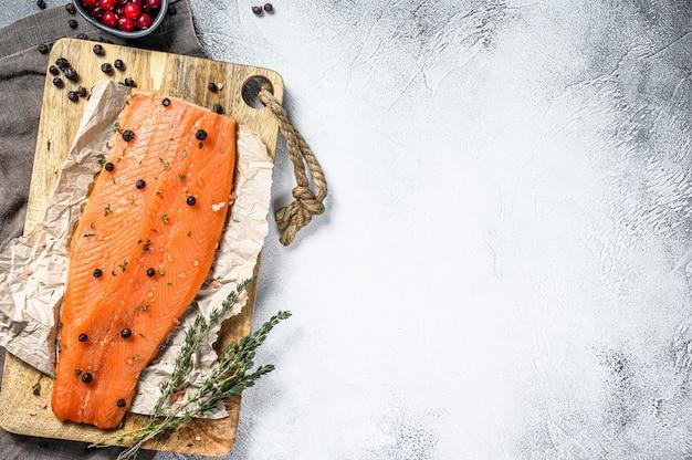 Cocinar filete de salmón salado en una tabla de cortar de madera con hierbas y especias.