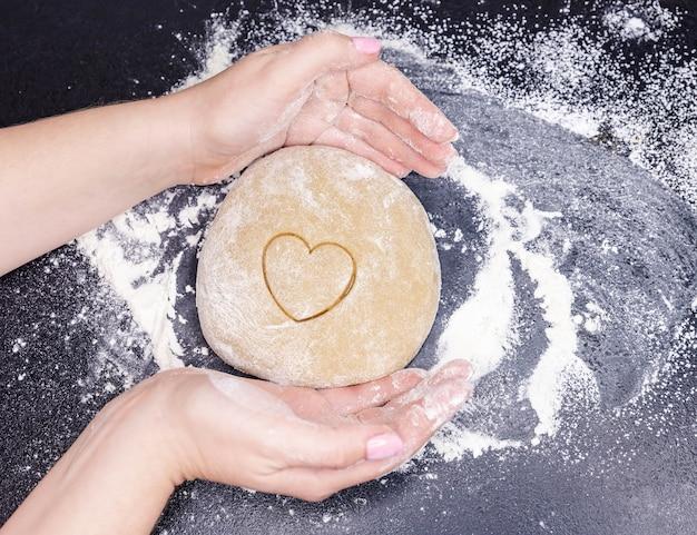 Cocinar galletas caseras de masa en forma de corazón y palabra amor en negro