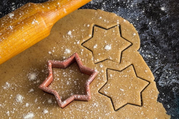 Cocinar galletas de jengibre de navidad con un rodillo sobre un fondo oscuro