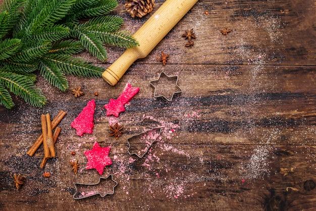 Cocinar galletas de jengibre rojo. pasteles tradicionales de navidad. fondo culinario festivo. abeto, especias, cortadores de galletas, masa cruda, rodillo, tablas de madera