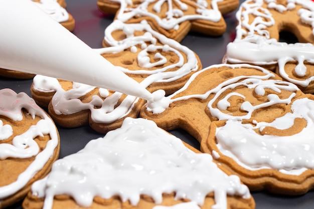 Cocinar galletas navideñas festivas: aplicar crema sobre la figura de santa claus.