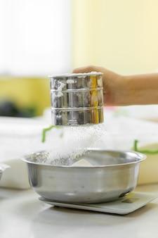 Cocinar hornear. cocinero tamiza la harina
