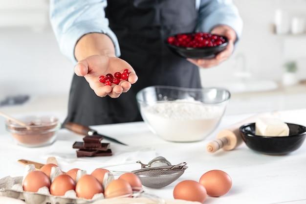 Cocinar con huevos en una cocina rústica contra el fondo de las manos de los hombres