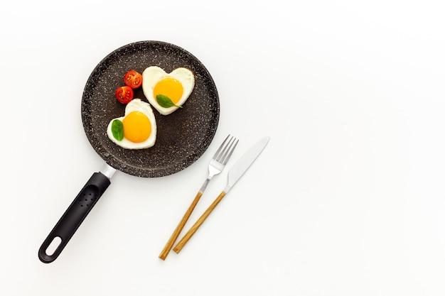 Cocinar huevos fritos en forma de corazón en una sartén