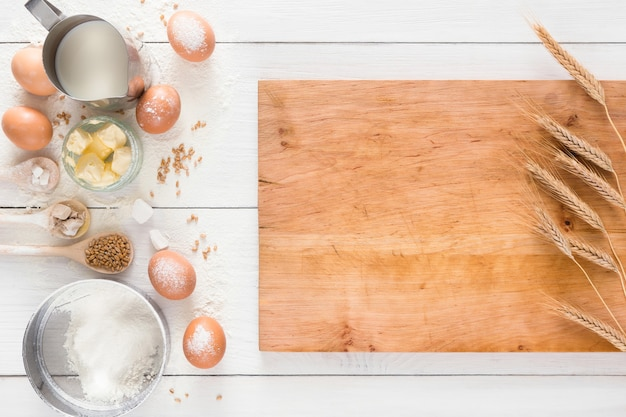 Cocinar ingredientes para masa de levadura y pastelería, huevos, harina y leche en madera rústica blanca. vista superior