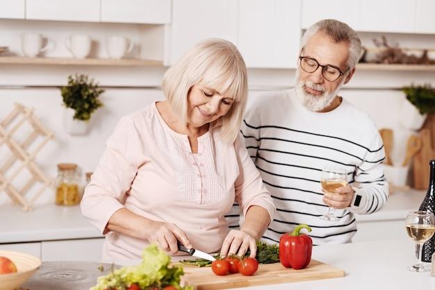 Cocinar juntos la cena familiar. sonriente pareja de ancianos encantadora de pie en la cocina y cocinando la cena mientras expresa felicidad y cuidado