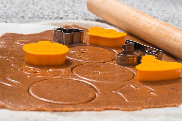 Cocinar pan de jengibre de halloween. dulces con cortadores de galletas y rodillo