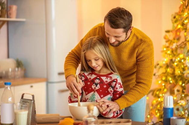 Cocinar con papá. niña y su papá revolviendo algo en un bol