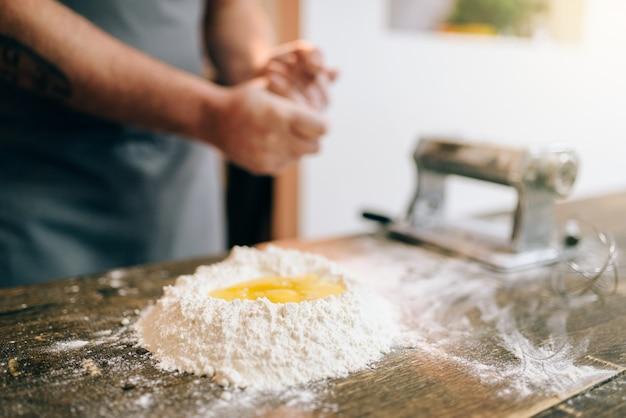 Cocinar la pasta casera, cocinero masculino que prepara la masa. huevo y manojo de harina en la mesa de madera