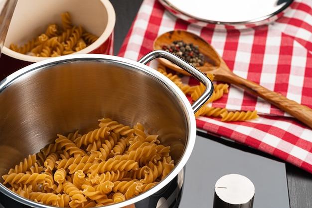 Cocinar la pasta en la cocina de casa en una olla de cerca