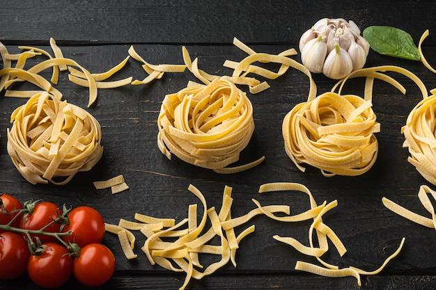 Cocinar pasta e ingredientes de tallarines, sobre mesa de madera negra