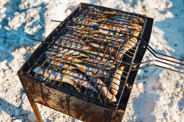 Cocinar pescado pequeño a la parrilla en la playa
