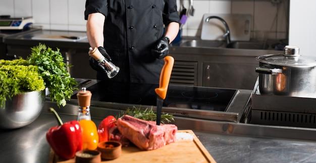 Cocinar de pie con pimentero en la mesa