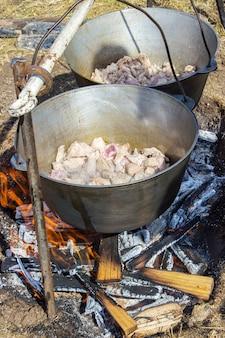 Cocinar plov en el caldero. sólo la carne en el caldero. cocina de campaña. cocina oriental.