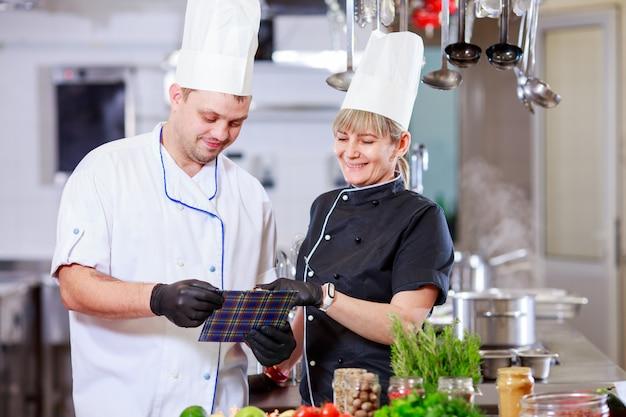 Cocinar preparando la cena en la cocina de un restaurante.