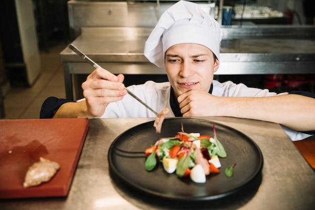 Cocinar preparando ensalada con carne frita en la mesa.