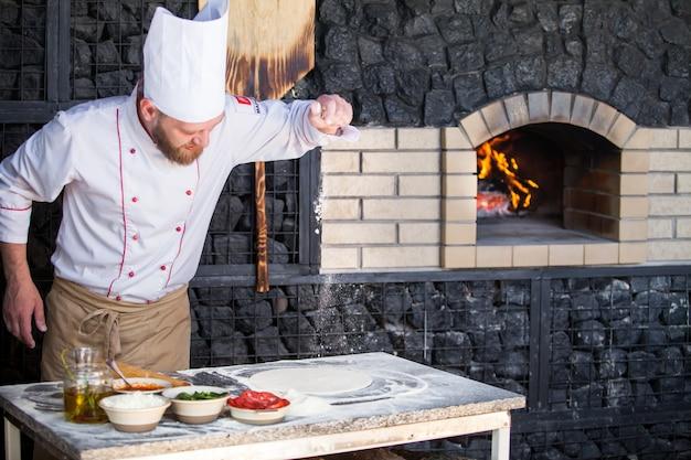 Cocinar preparando pizza en un restaurante.