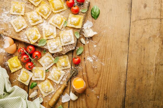 Cocinar ravioles italianos en la mesa de madera
