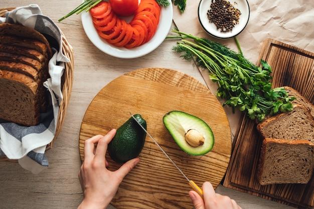 Cocinar un sándwich saludable con aguacate y tomate en casa en la cocina.