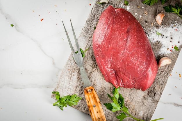 Cocinar solomillo de ternera. gran trozo entero de filete de ternera en una vieja tabla de cortar con un tenedor para carne, especias (sal, pimienta, perejil, ajo, cebolla, tomate). vista superior