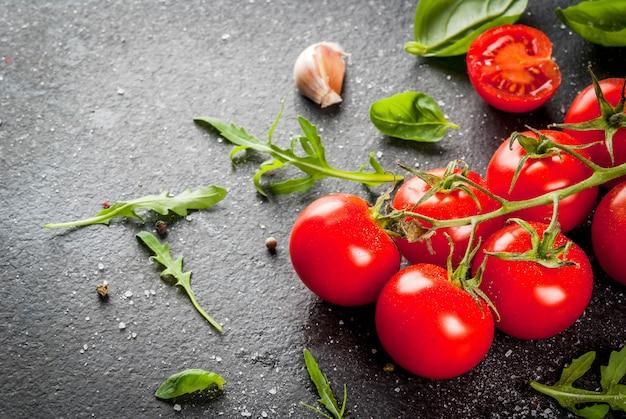 Cocinar, superficie. ingredientes para cocinar. especias (sal pimienta) verdes (albahaca perejil rúcula) y cóctel de tomates cherry sobre una mesa de piedra negra. copia espacio