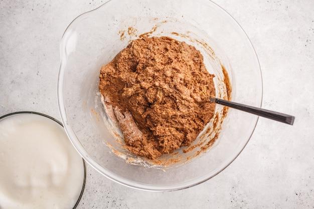 Cocinar la torta de chocolate del vegano con aquafaba en el bol de vidrio, visión superior.