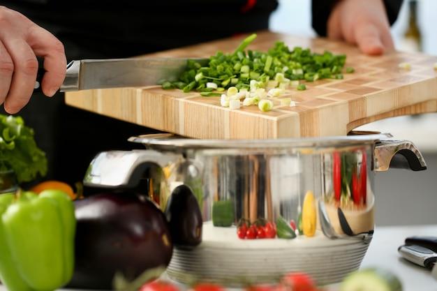 Cocine agregando verduras a la olla