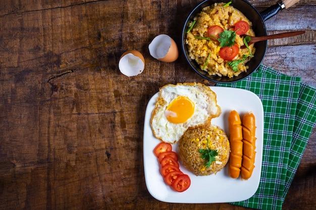 Cocine el arroz frito americano en una sartén, servido con huevos fritos y salchichas.