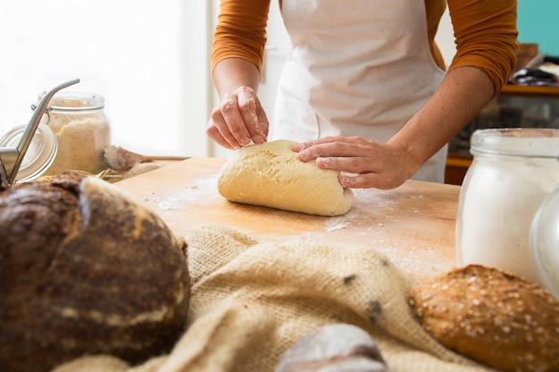 Cocine de pie cerca de la mesa y formando masa sobre tabla de madera