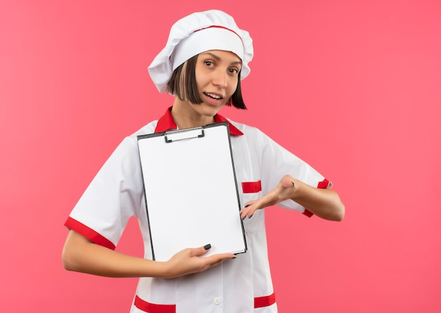 Cocinera joven complacida en uniforme de chef sosteniendo y apuntando con la mano al portapapeles aislado sobre fondo rosa