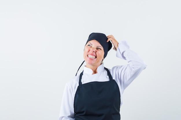 Cocinera rascándose la cabeza en uniforme, delantal y mirando vacilante, vista frontal.