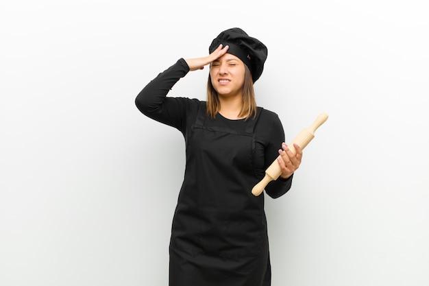Cocinera sintiéndose estresada y ansiosa, deprimida y frustrada con dolor de cabeza, levantando ambas manos a la cabeza