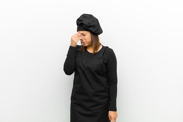 Cocinera sintiéndose estresada, infeliz y frustrada, tocando la frente y sufriendo migraña de dolor de cabeza severo contra la pared blanca