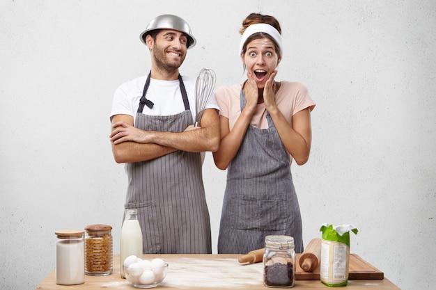 Cocinera sorprendida con expresión de asombro mira a la cámara mientras se da cuenta de que tiene fecha límite