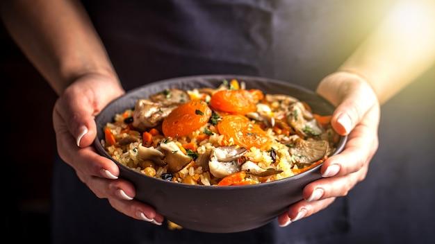 La cocinera sostiene un plato con un plov vegetariano.