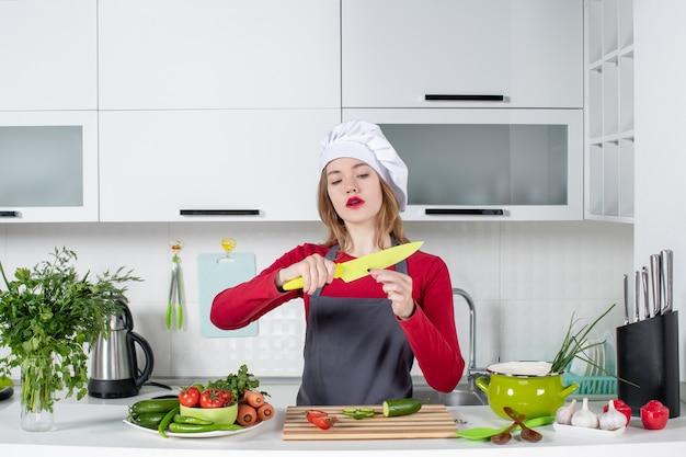 Cocinera vista frontal en delantal con cuchillo amarillo
