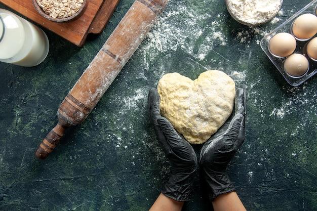 Cocinera de vista superior trabajando con masa en forma de corazón sobre superficie gris oscuro