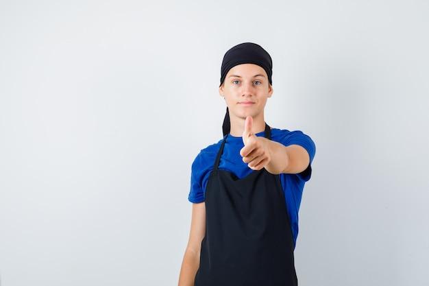 Cocinero adolescente masculino apuntando al frente en camiseta, delantal y mirando decidido. vista frontal.