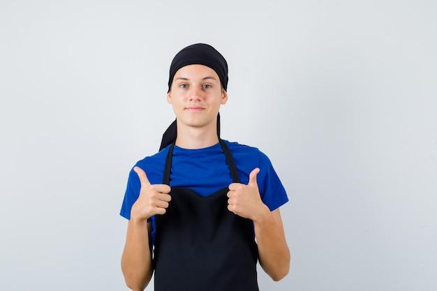Cocinero adolescente masculino mostrando gesto de parada en camiseta, delantal y mirando contento, vista frontal.