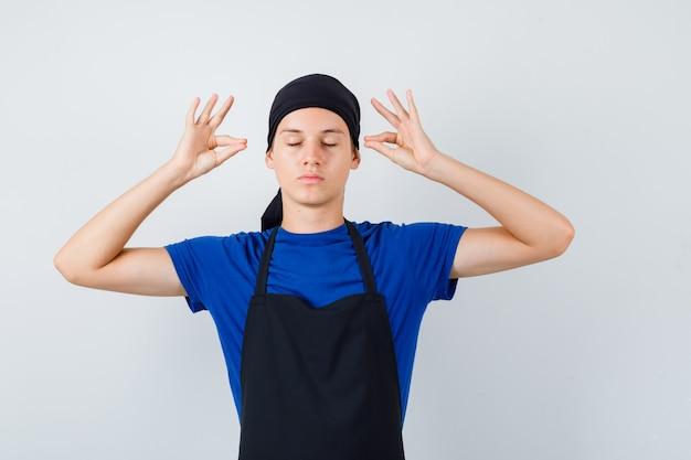Cocinero adolescente masculino mostrando mudra firmar en camiseta, delantal y mirando pacífica, vista frontal.