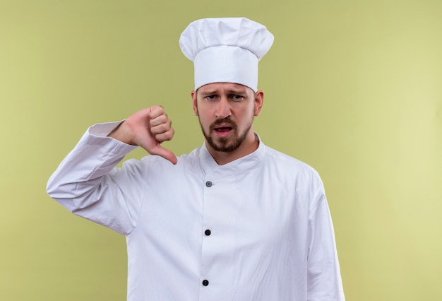 Cocinero de chef masculino profesional autosatisfecho en uniforme blanco y sombrero de cocinero apuntando a sí mismo de pie sobre fondo verde