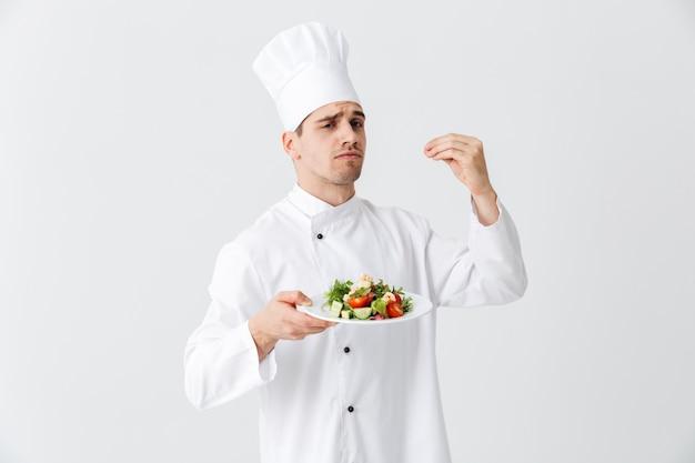 Cocinero cocinero hombre serio vistiendo uniforme mostrando ensalada verde fresca en un plato aislado sobre la pared blanca