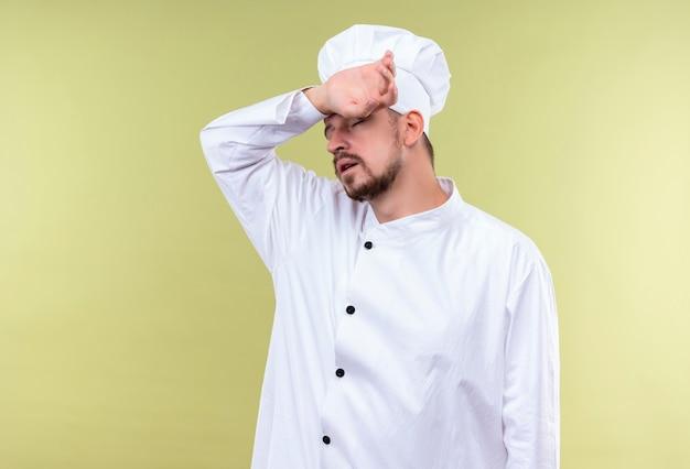 Cocinero cocinero profesional masculino en uniforme blanco y sombrero de cocinero con aspecto cansado y con exceso de trabajo tocando su cabeza sobre fondo verde